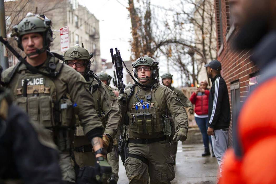 Police officers arrive at the scene following reports of gunfire, Tuesday, Dec. 10, 2019, in Je ...