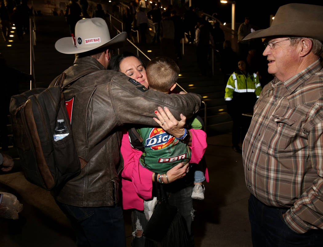 Missi Henderson, 43, of Winfield, Kan., gets a hug from National Finals Rodeo roper Coleman Pro ...