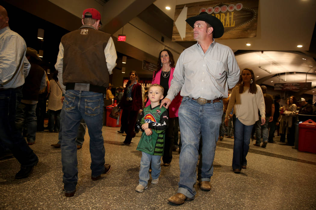 Missi Henderson, 43, of Winfield, Kan., walks to her seats with son Murphy, 4, and husband Shan ...