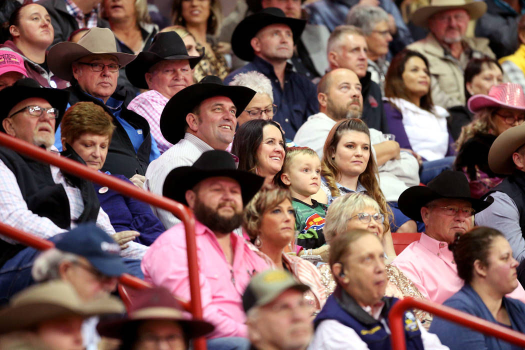 Missi Henderson, 43, of Winfield, Kan., watches the National Finals Rodeo with son Murphy, 4, a ...
