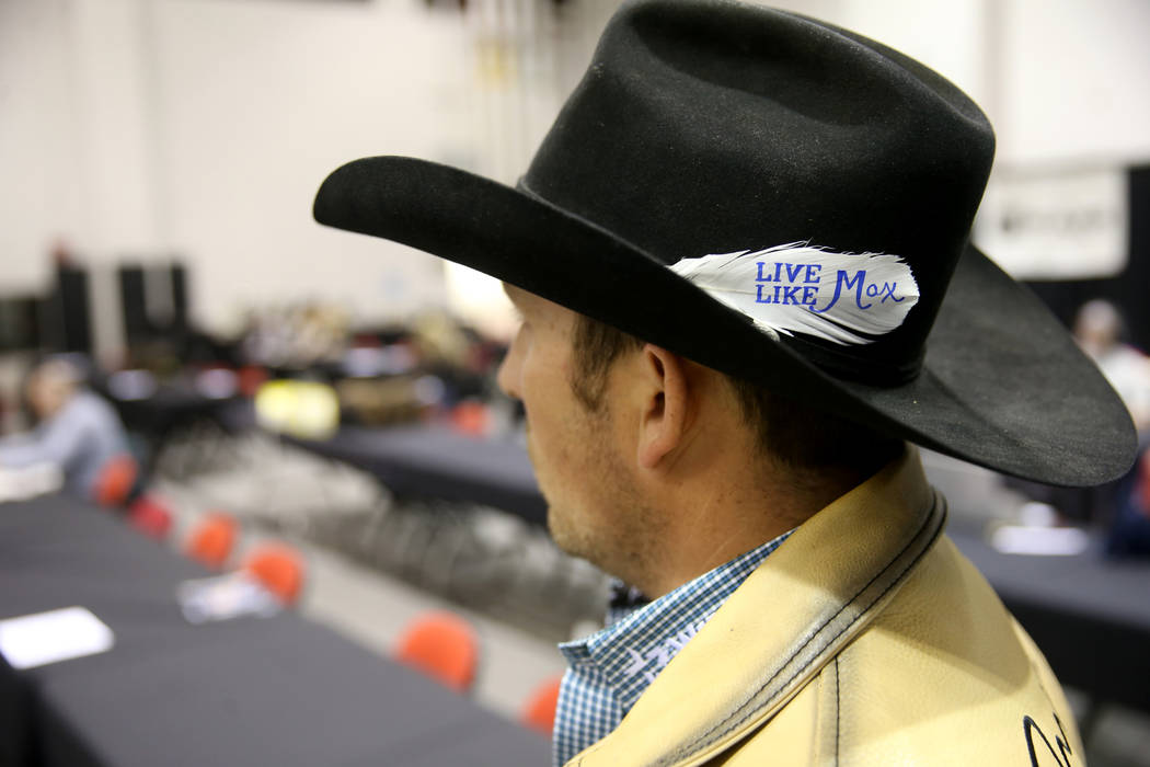 "Steer wrestler Riley Duvall dons a ""Live Like Max"" white before the sixth go-round of ..."
