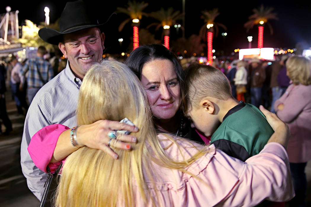 Missi Henderson, 43, of Winfield, Kan., gets a hug from family friend Susan Kanode while holdin ...