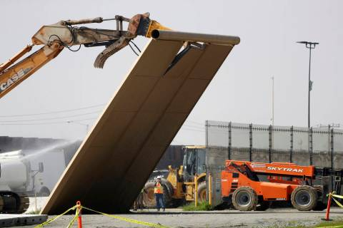 FILE - In this Feb. 27, 2019, file photo, a border wall prototype falls during demolition at th ...