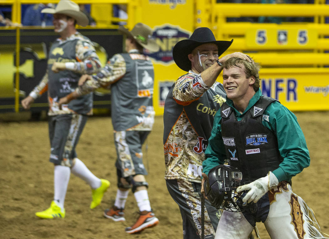 Boudreaux Campbell of Crockett, Texas, is congratulated by a bullfighter after riding Priefert' ...