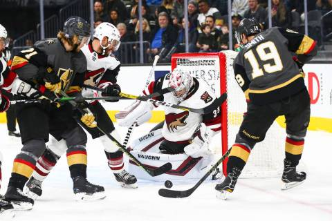Arizona Coyotes goaltender Darcy Kuemper (35) blocks a shot from Golden Knights' Reilly Smith ( ...