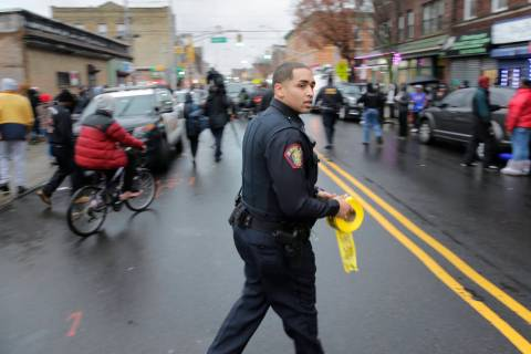 A police officer pushes pedestrians back from the scene of a shooting in Jersey City, N.J., Tue ...