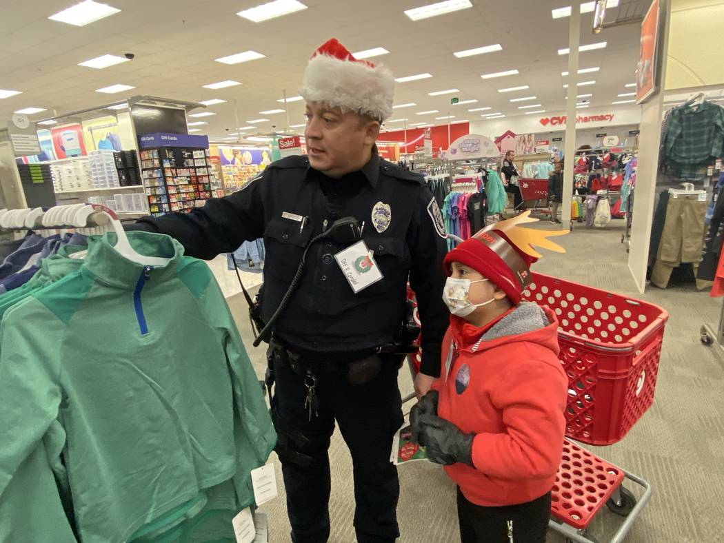 North Las Vegas patrol officer Edwin Corales shows Aiden Pinacruz some clothes he might want to ...