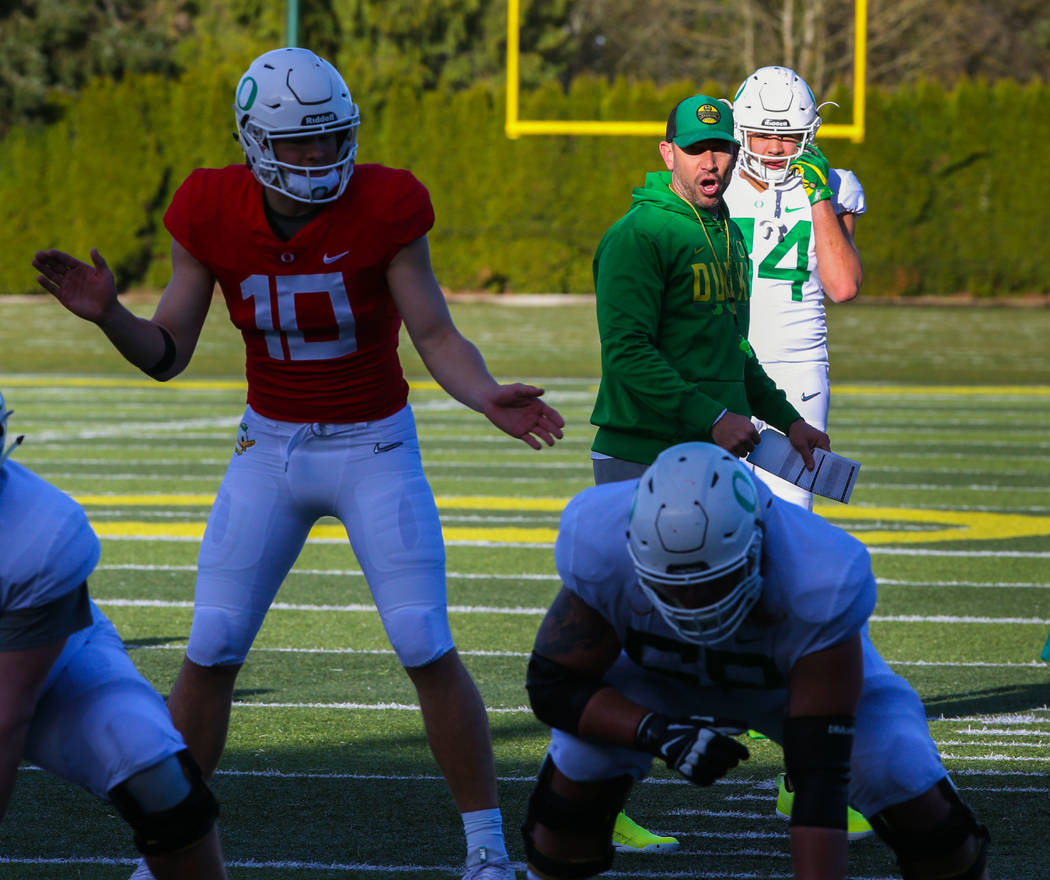 Oregon Offensive Coordinator Marcus Arroyo, center, works with the quarterbacks and the offense ...