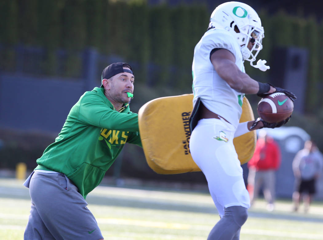 Oregon Offensive Coordinator Marcus Arroyo blocks running back Taj Griffin during a passing dri ...