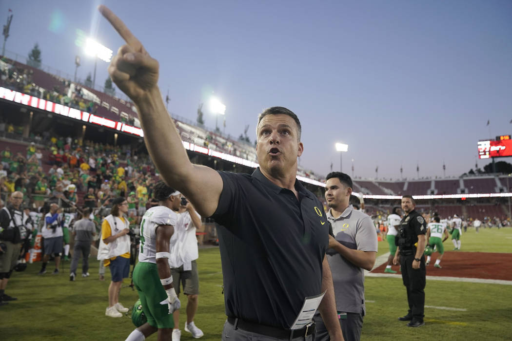 Oregon head coach Mario Cristobal points to fans as he walks off the field after an NCAA colleg ...