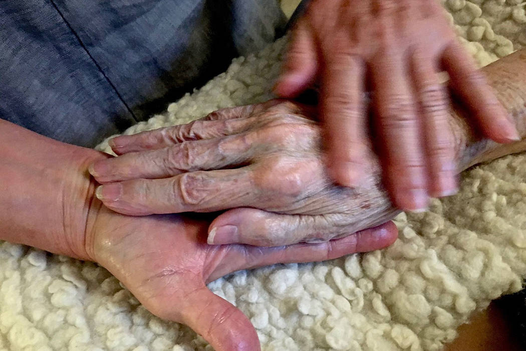In this 2016 photo provided by Thomas Marrinson, Allison Beach holds the hand of her ailing mot ...