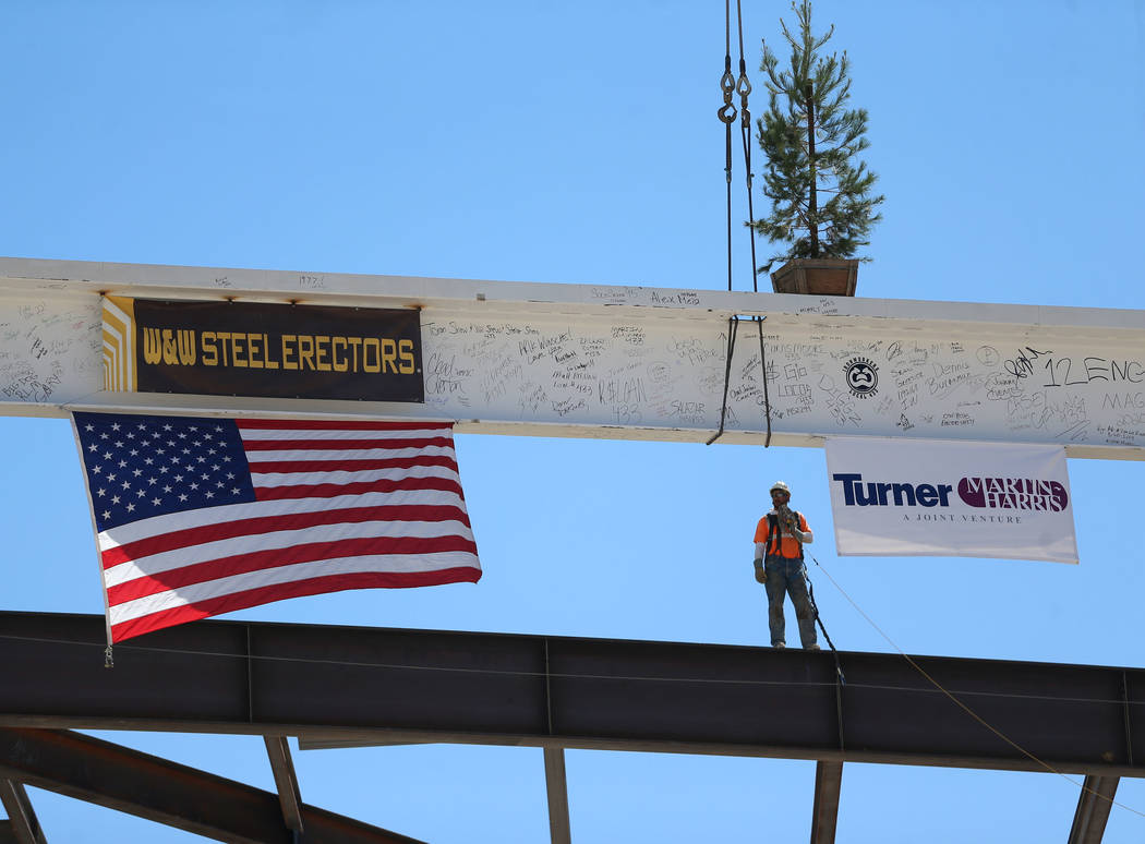 Workers hoist the last high beam on top of the future Las Vegas Convention Center exhibit hall ...
