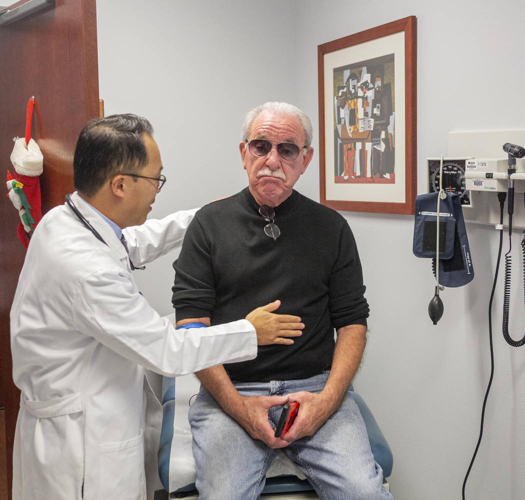 Dr. Anthony Nguyen, left, does a routine checkup on 73-year-old Fred Warnick, the first patient ...