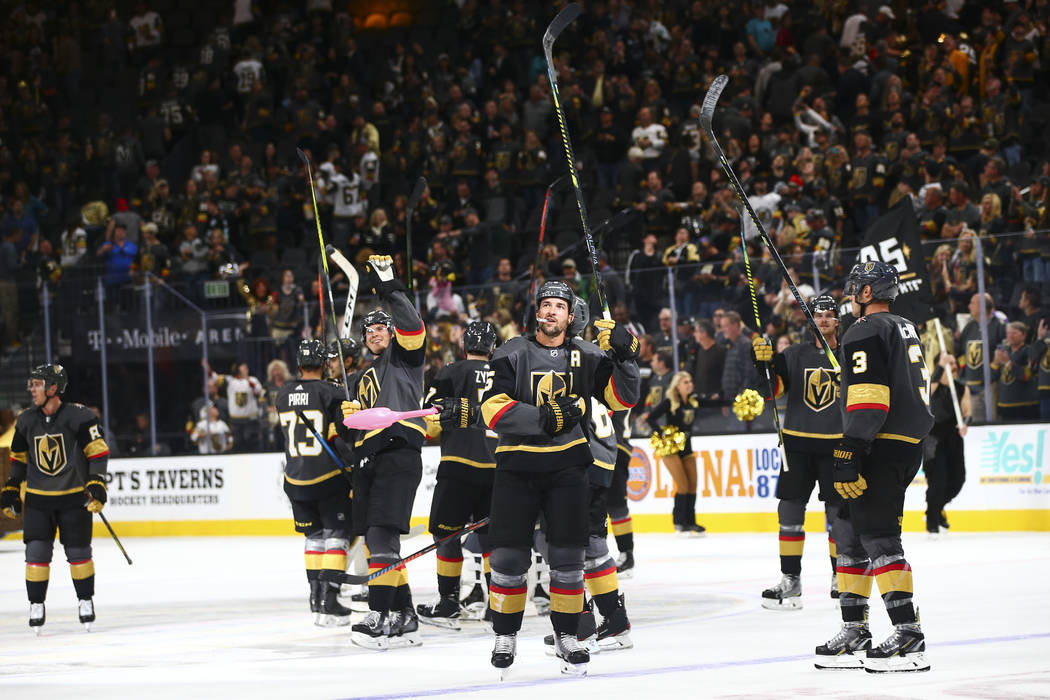 Golden Knights players celebrate their 4-1 victory over the San Jose Sharks in an NHL season-op ...