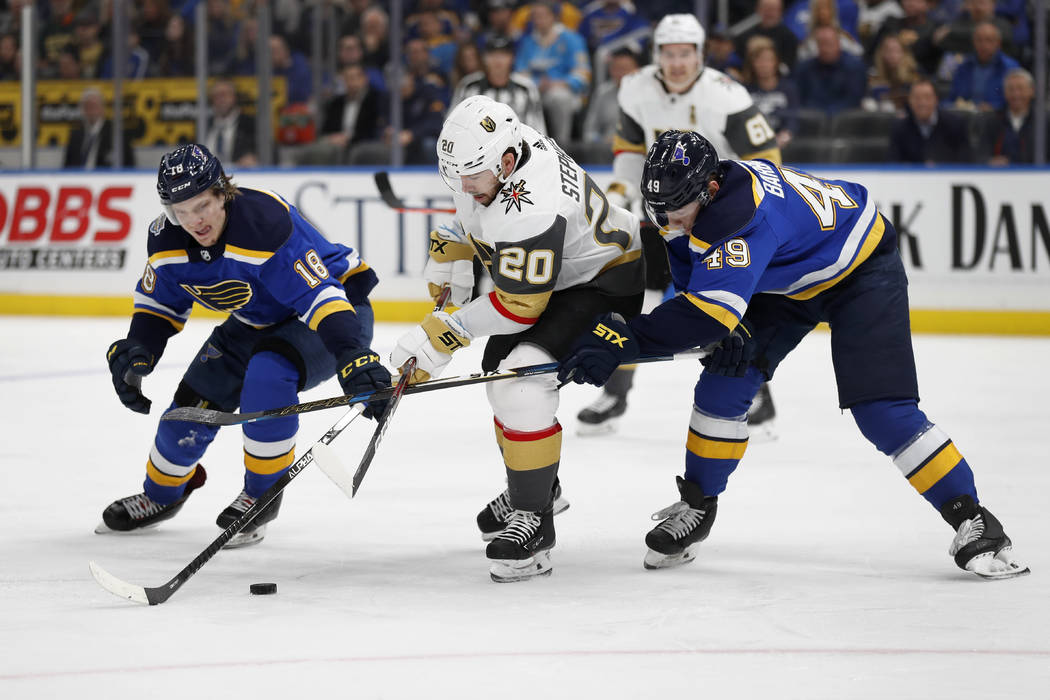 Vegas Golden Knights' Chandler Stephenson (20) reaches for a puck between St. Louis Blues' Robe ...