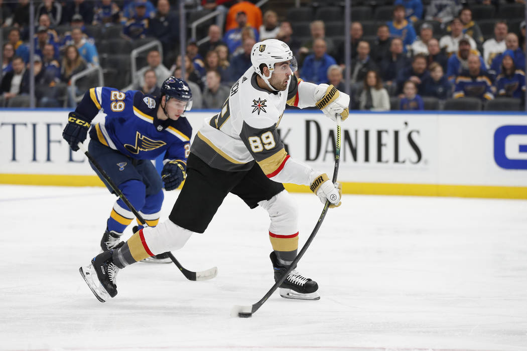 Vegas Golden Knights' Alex Tuch (89) shoots as St. Louis Blues' Vince Dunn (29) defends during ...