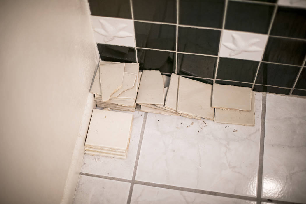 John and Mary Bodimer have gathered tiles that have fallen from the leaking ceiling in the gues ...