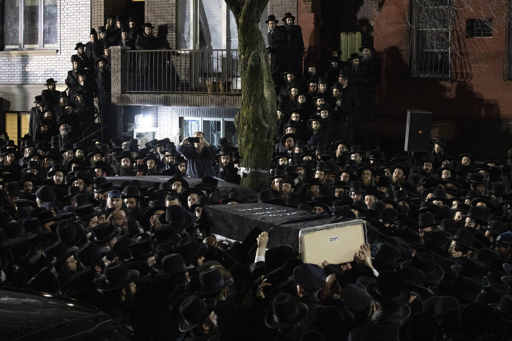 Orthodox Jewish men carry Moshe Deutsch's casket outside a Brooklyn synagogue following his fun ...