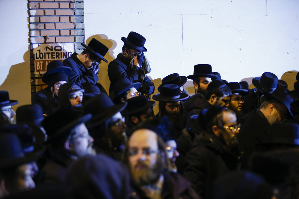 Orthodox Jewish men mourn during the funeral service of Mindel Ferencz who was killed in a kosh ...