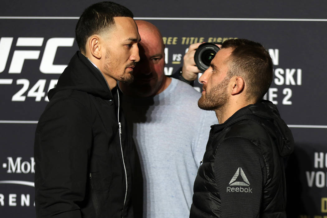 UFC featherweight champion Max Holloway engages in a staredown with his opponent, Alexander Vol ...
