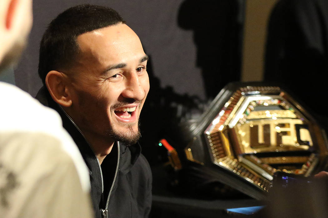 UFC featherweight champion Max Holloway laughs during a scrum with reporters at a UFC 245 media ...
