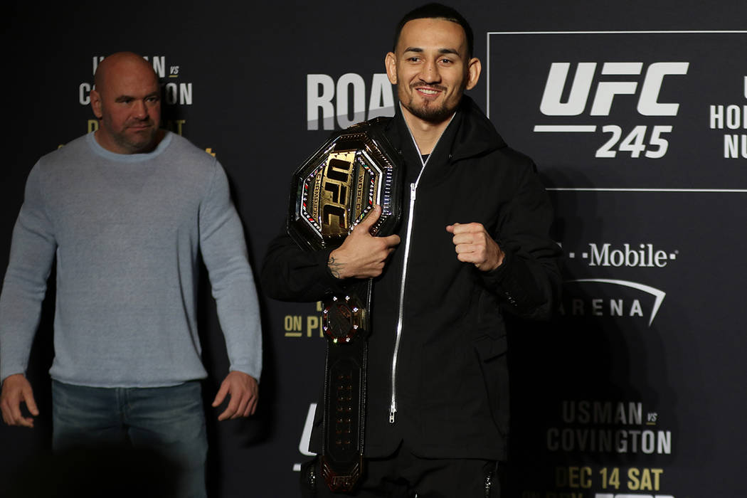 UFC featherweight champion Max Holloway poses during a UFC 245 media event as UFC president Dan ...