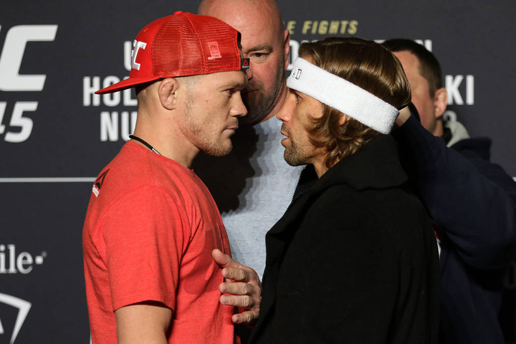 UFC bantamweights Petr Yan and Urijah Faber, right, staredown as UFC president Dana White keeps ...