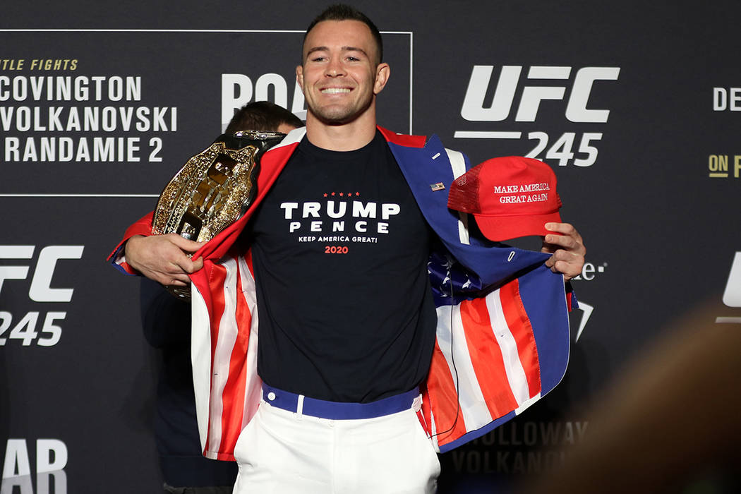 UFC welterweight Colby Covington poses holding his old title belt and Trump hat during a UFC 24 ...