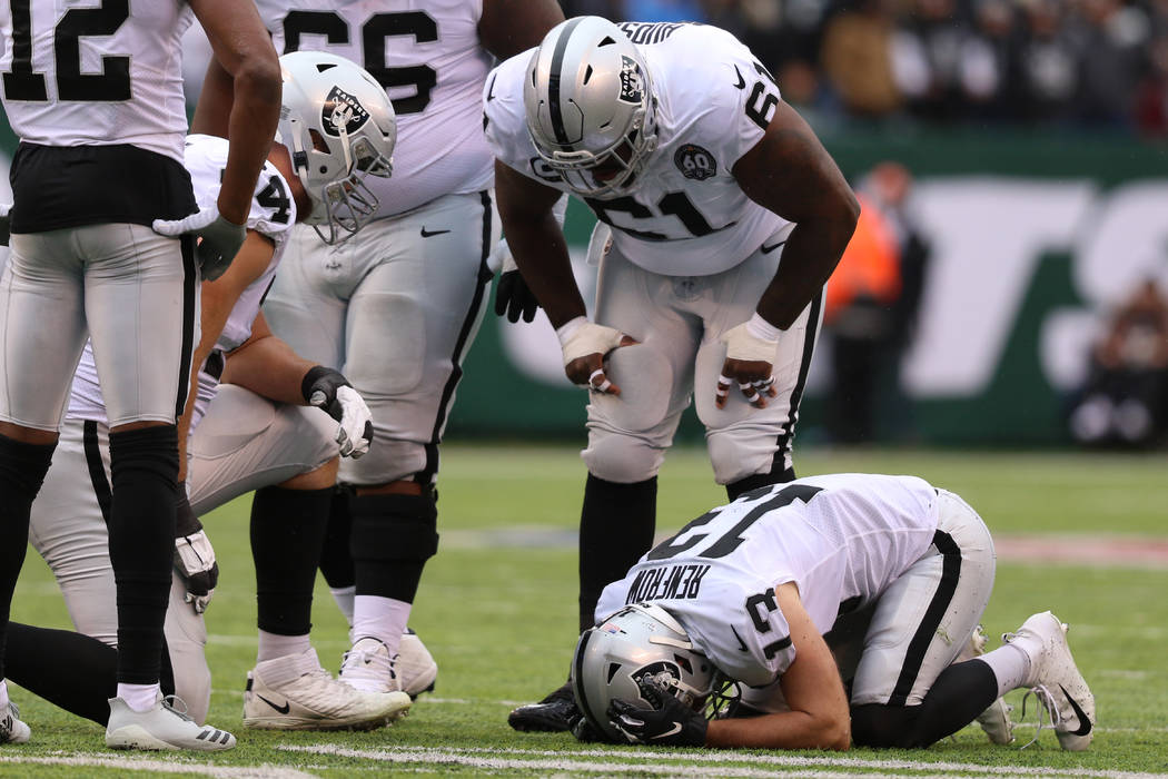 Oakland Raiders wide receiver Hunter Renfrow (13) remains on the field after colliding with a N ...
