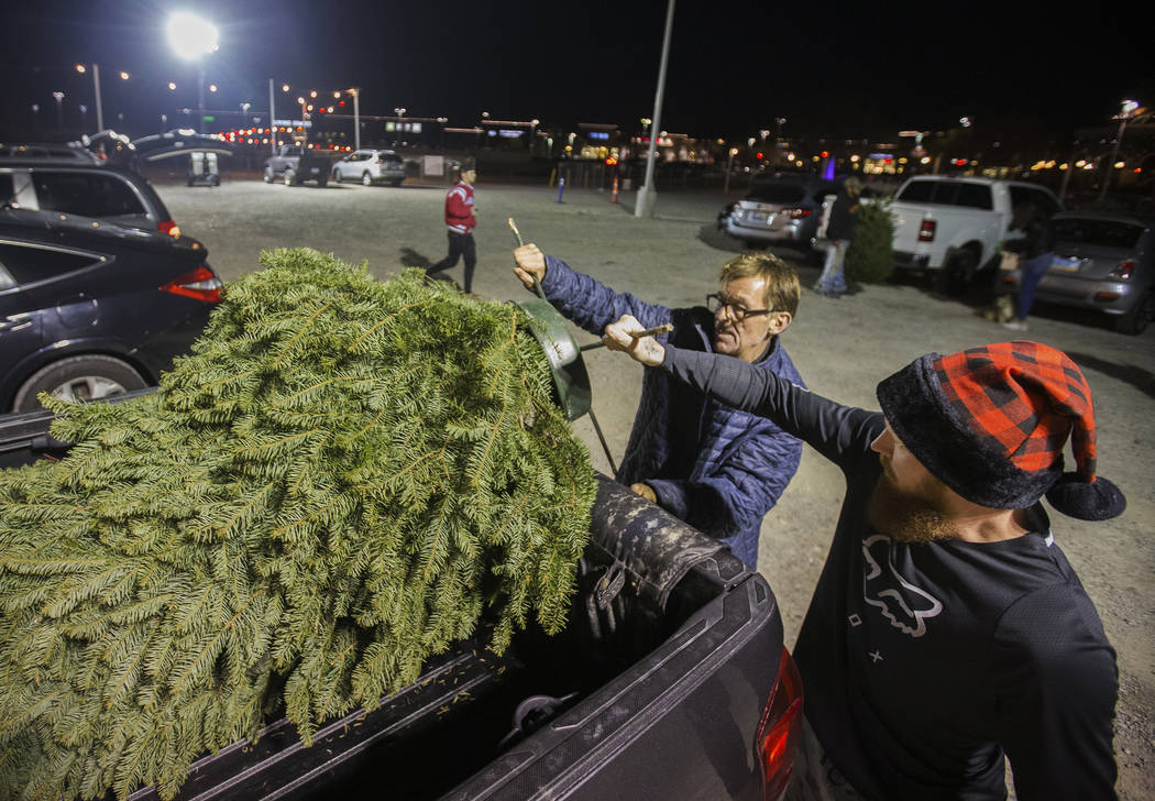 Jay Rogers, middle, helps Justin Critser load a Christmas tree into Crister's truck on Wednesda ...