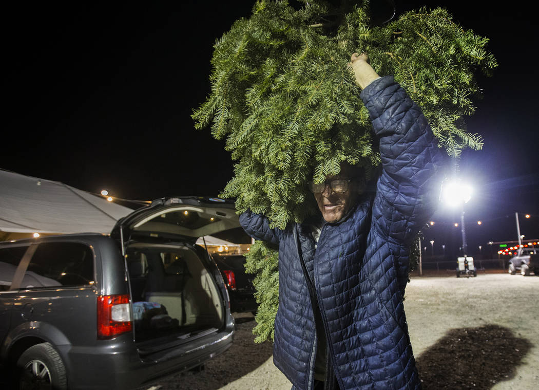 Jay Rogers carries a newly bought Christmas tree to a customers car on Wednesday, Dec. 11, 2019 ...