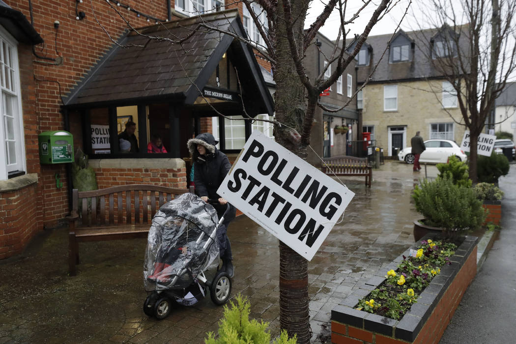 A sign hangs from a tree as rain falls outside a polling station at Merry Bells Village Hall in ...