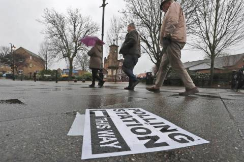 A polling station signpost lies on the pavement as voters approach a polling station in Twicken ...