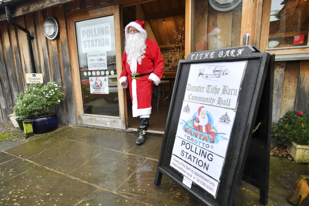 A man dressed as Father Christmas walks from his grotto at the Dunster Tithe Barn near Minehead ...