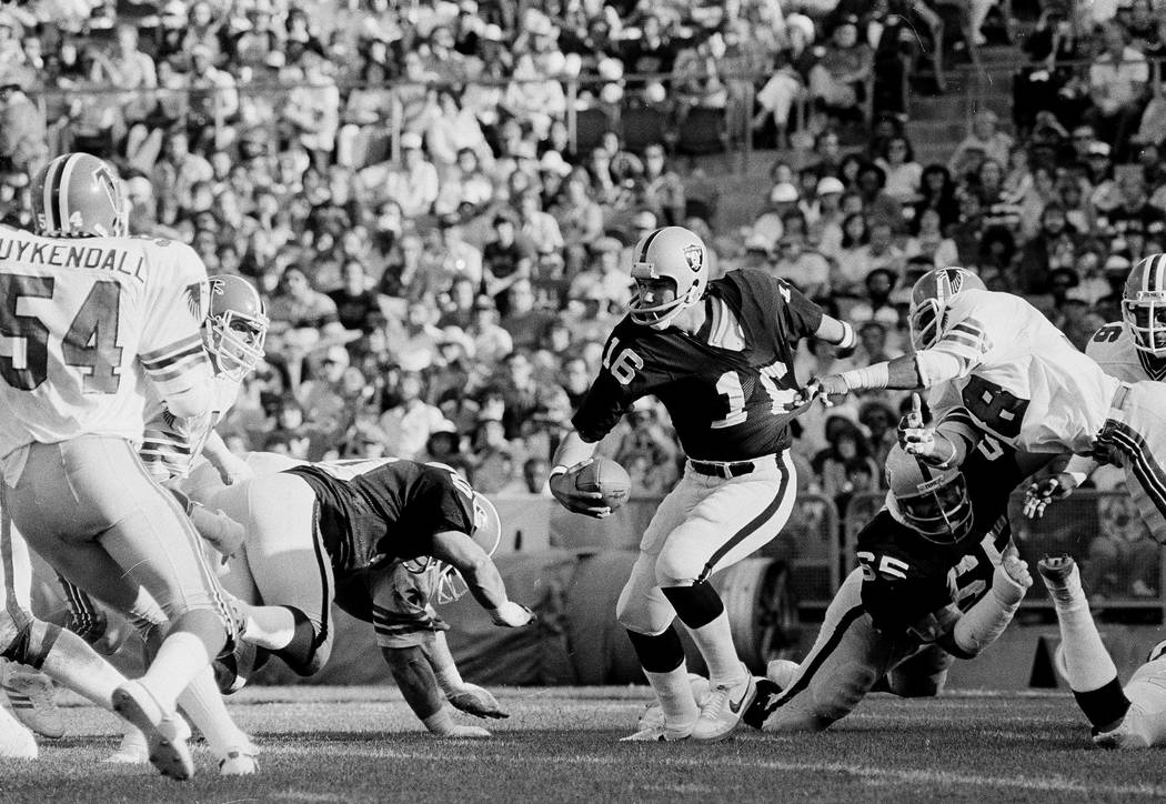 Oakland Raiders quarterback Jim Plunkett (16) gets his shirt pulled by Atlanta Falcons Joel Wil ...