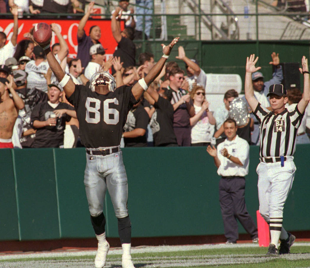 "Oakland Raiders Raghib ""Rocket"" Ismail raises his arms in the end zone after catching a 44-yard ..."
