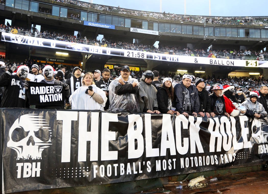 The fans in the Black Hole pose before the start of an NFL game between the Oakland Raiders and ...