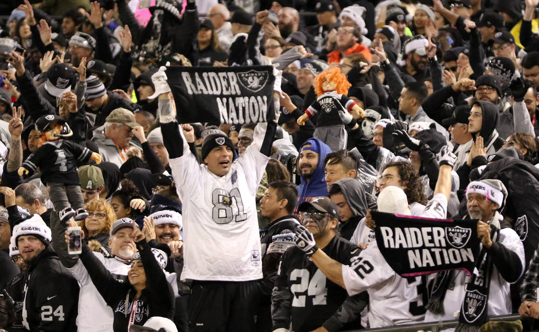 Oakland Raiders fans hold up dolls and towels during the first half of an NFL game against the ...