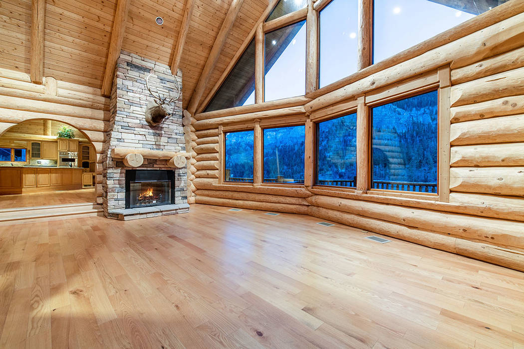 Berkshire Hathaway Home Services The living room has plenty of windows and a rustic wood-burnin ...