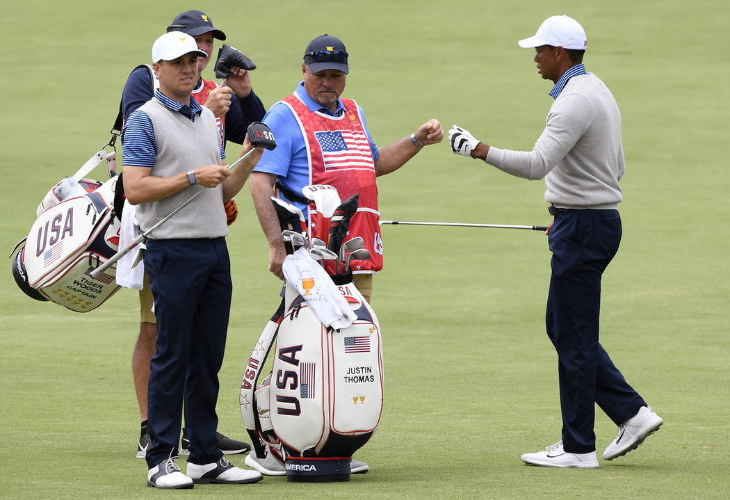 U.S. team player and captain Tiger Woods, right, and playing partner Justin Thomas, left, walk ...