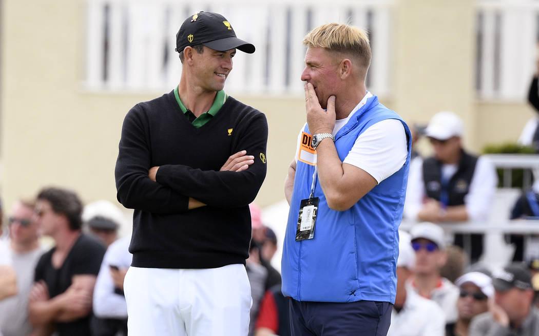 International team player Adam Scott of Australia, left, talks with former cricket player Shane ...