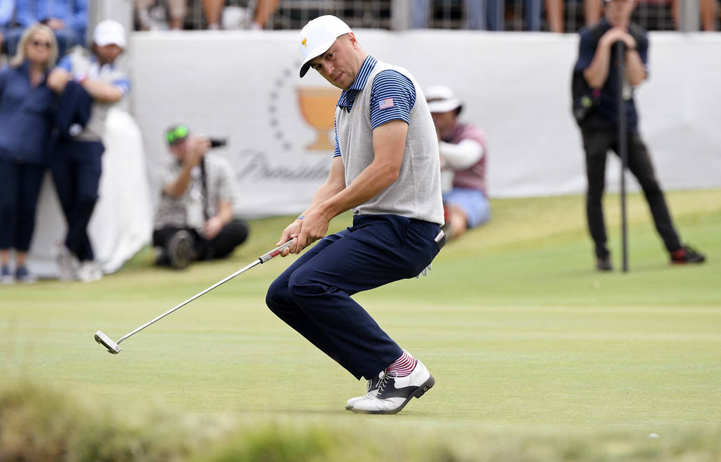 U.S. team player Justin Thomas crouches as he misses a putt on the 16th green in their foursome ...