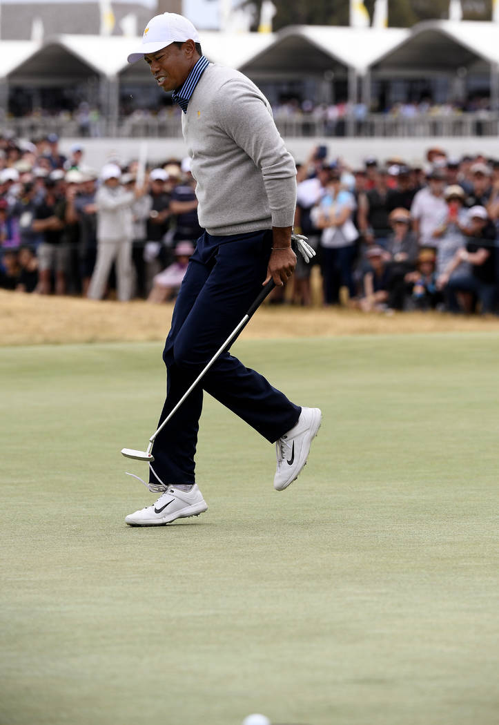 U.S. team player and captain Tiger Woods skips as he misses a putt on the 17th green in their f ...