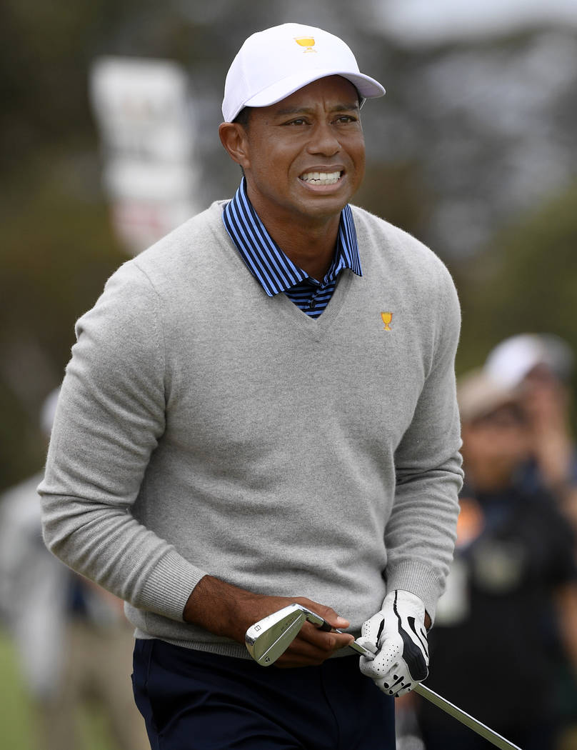 U.S. team player and captain Tiger Woods watches his shot on the 18th hole in their foursomes m ...