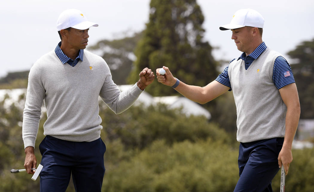 U.S. team player and captain Tiger Woods, left, and playing partner Justin Thomas fist bump aft ...