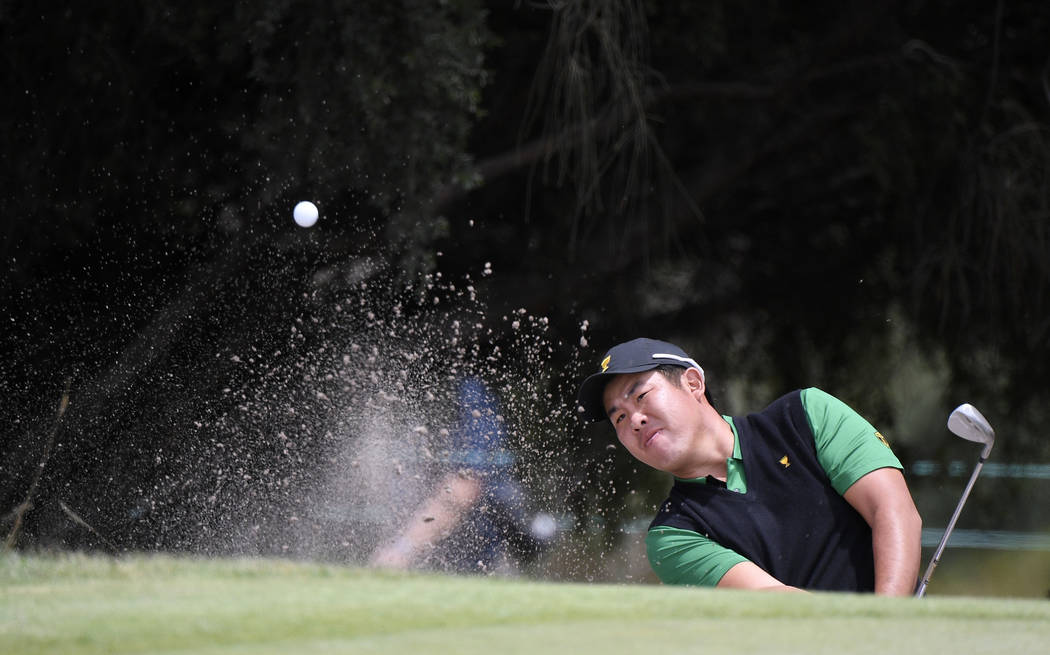 International team player Byeong Hun An of South Korea plays from a bunker at the 9th green in ...