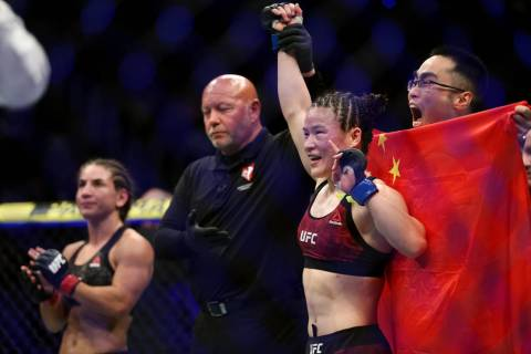 Weili Zhang, right, raises her hand in victory by unanimous decision against Tecia Torres in th ...