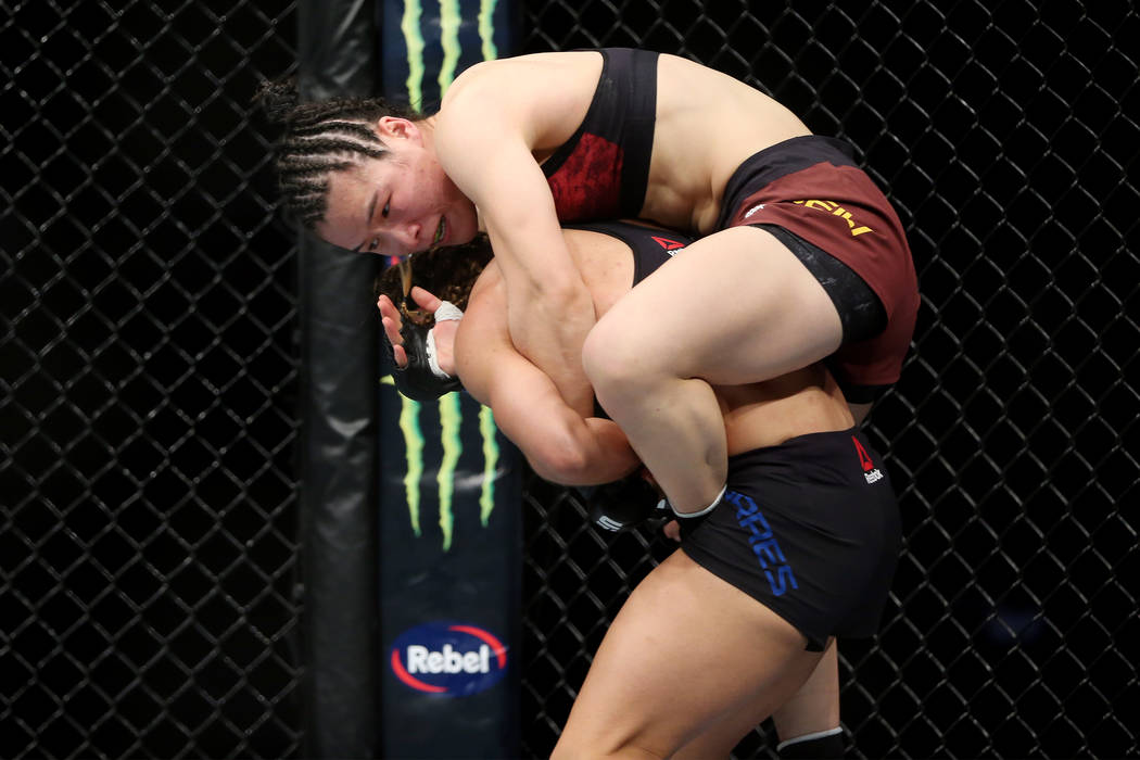 Weili Zhang, top, grabs to Tecia Torres in the womenÕs strawweight bout during UFC 235 at ...
