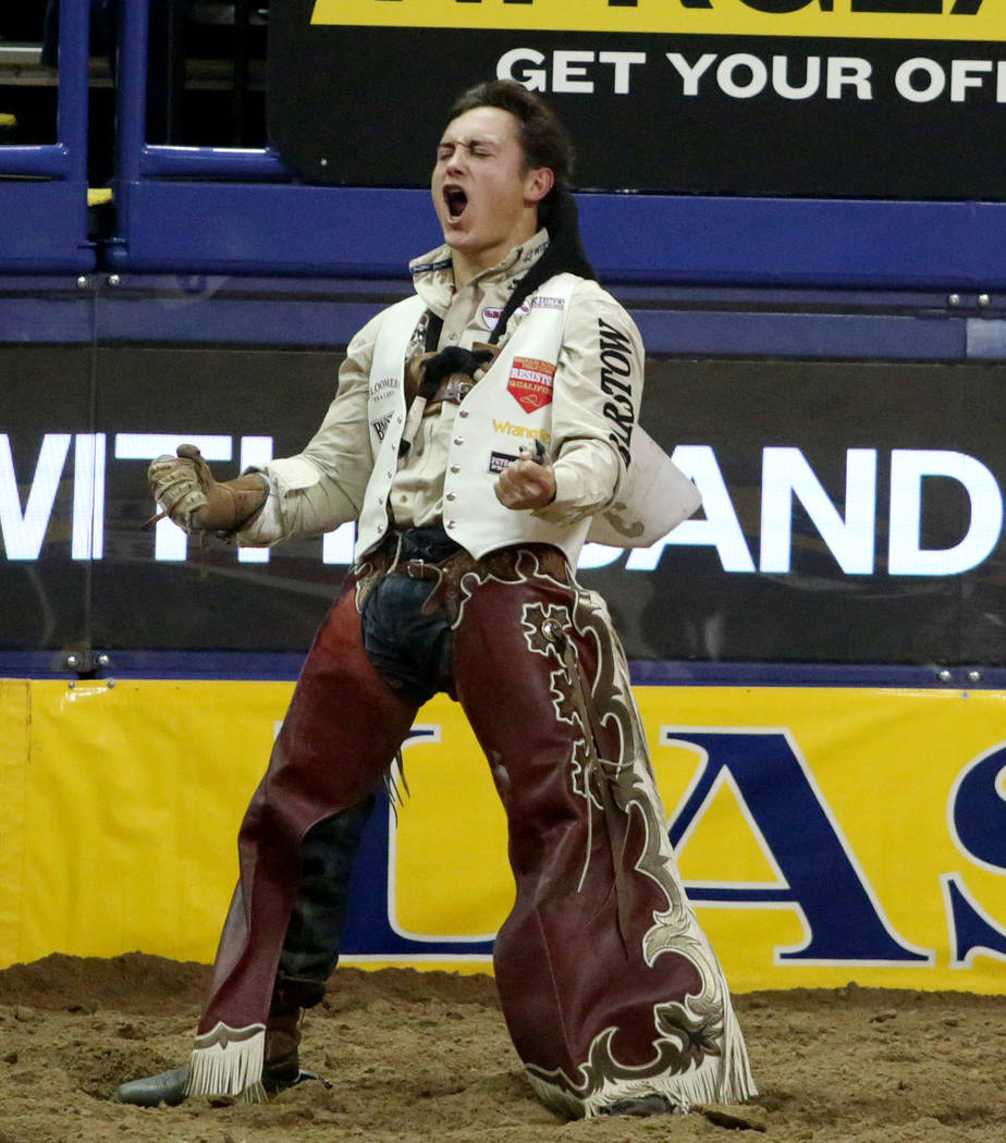 Clayton Biglow of Clements, Calif. celebrates after placing first in bareback riding in the eig ...
