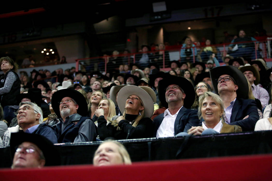 Attendees watch the replay of Team Roping during the eighth go-round of the Wrangler National F ...
